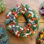 Örökzöld terméses koszorú piros-fehér virágokkal